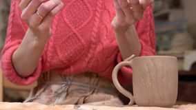 Close up do ceramist da mulher peça pequena aderindo-se da argila ao copo cru da argila video estoque