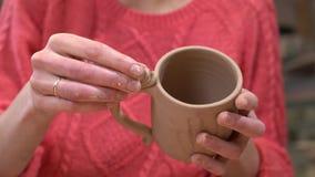 Close up do ceramist da mulher que instecting e que faz toques finais ao copo cru da argila em suas mãos vídeos de arquivo