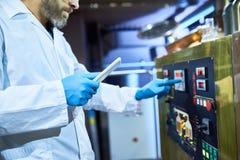 Close-up do cervejeiro no revestimento do laboratório que trabalha no equipamento moderno no pl fotos de stock royalty free