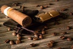 Close-up do charuto e do isqueiro com os feijões de café na madeira áspera imagens de stock royalty free
