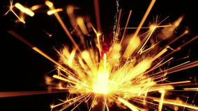 Close-up do chuveirinho do fogo de artifício que queima-se no fundo preto, ano novo feliz do partido do cumprimento das felicitaç