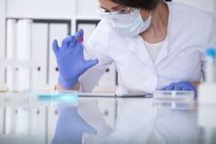 Close-up do cientista fêmea profissional nos monóculos protetores que fazem a experiência com os reagentes no laboratório Foto de Stock Royalty Free
