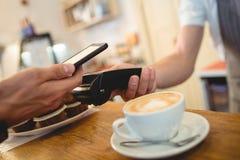 Close-up do cliente com telefone celular e do barista com leitor de cartão Imagem de Stock Royalty Free