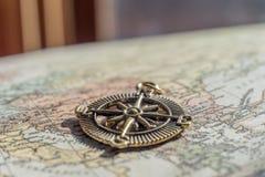 Close up do compasso do vintage no mapa de Velho Mundo na frente do cu pesado Fotos de Stock