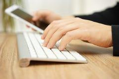 Close up do computador de utilização adulto novo e do telefone celular esperto em Imagens de Stock Royalty Free