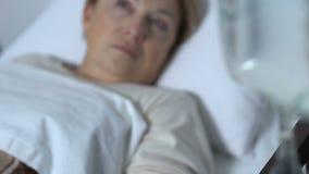 Close-up do conta-gotas perto do paciente fêmea idoso que acorda após o coma, amnésia filme
