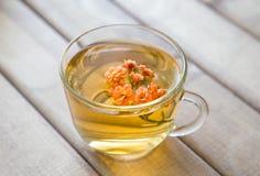 Close up do copo do chá com a flor brilhante na tabela de madeira Ainda vida com copo de chá Fotografia de Stock Royalty Free