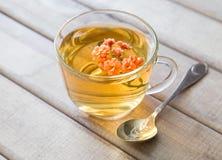 Close up do copo do chá com a flor brilhante na tabela de madeira com colher Ainda vida com copo de chá Fotografia de Stock