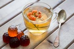 Close up do copo do chá com a flor brilhante na tabela de madeira com colher e doce de fruta Ainda vida com copo de chá Imagem de Stock