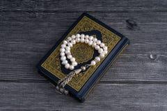 Close up do Corão/Alcorão com grânulos ou de Tasbih/rosário santamente sobre o fundo de madeira Imagem de Stock Royalty Free