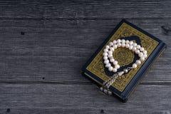 Close up do Corão/Alcorão com grânulos ou de Tasbih/rosário santamente sobre o fundo de madeira Fotos de Stock Royalty Free