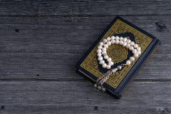 Close up do Corão/Alcorão com grânulos ou de Tasbih/rosário santamente sobre o fundo de madeira Foto de Stock Royalty Free