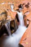 Close up do corte pequeno da cascata através do arenito Imagens de Stock Royalty Free