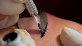 Close-up do cosmetologist que faz o procedimento microblading Composi??o permanente Tattooing permanente das sobrancelhas filme