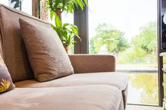 Close up do coxim no sofá pela janela na sala de visitas em casa fotos de stock