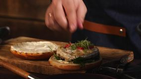 Close-up do cozinheiro chefe masculino no avental azul que adiciona verdes em um bolo de Hamburger fritado Metragem conservada em filme