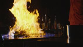 Close-up do cozinheiro chefe que cozinha um prato principal do banquete Vegetais e carne com mostra do fogo