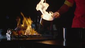 Close-up do cozinheiro chefe que cozinha um prato principal do banquete Vegetais e carne com mostra do fogo video estoque