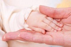 Close-up do dedo da matriz da terra arrendada da mão do bebê Imagens de Stock
