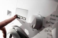 Close up do dedo da mulher com o botão de empurrão do verniz para as unhas na máquina de lavar fotos de stock