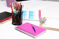 Close up do desktop branco com portátil, vidros, copo de café, blocos de notas e outros artigos no fundo obscuro da cidade Foto de Stock