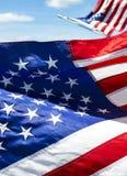 Close up do detalhe de bandeira americana bordada com outra borrada sobre no fundo contra o céu azul Imagem de Stock