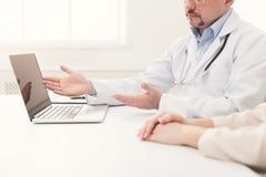 Close up do doutor e do paciente que sentam-se na mesa fotografia de stock