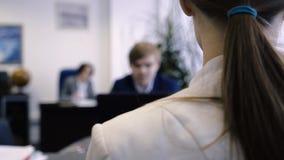 Close-up do escritório sobre o ombro da jovem mulher Vista traseira sobre o ombro focalizado do empregado novo do escritório na m vídeos de arquivo