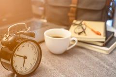 Close-up do estilo retro do vintage do pulso de disparo do preto do alarme com café branco do copo imagens de stock