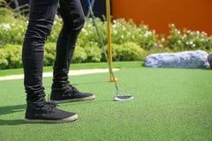 Close-up do furo do mini golfe com bastão e bola Foto de Stock