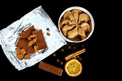 Close-up do gelado de chocolate, do chocolate e das amêndoas de leite, dos feijões de café, da vara da canela e de uma fatia de l fotos de stock royalty free
