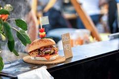 Close up do hamburguer na placa de madeira no mercado aberto do alimento em Ljubljana, Eslovênia Foto de Stock Royalty Free