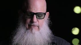 Close-up do homem calvo com barba usando o telefone celular fora na noite filme
