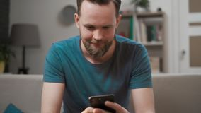Close-up do homem caucasiano que usa o smartphone m?vel moderno que senta-se em um sof? em casa, guardando o telefone celular em  vídeos de arquivo