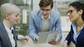 Close-up do homem de negócios alegre que fala e que discute sobre o relatório financeiro com o assento fêmea dos colegas do negóc