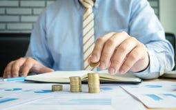 Close-up do homem de negócios Hand Put Coins à pilha de moedas no fina fotos de stock