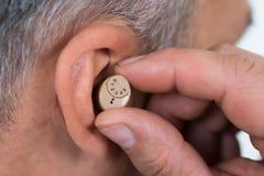 Close up do homem de negócios Inserting Hearing Aid na orelha imagem de stock royalty free