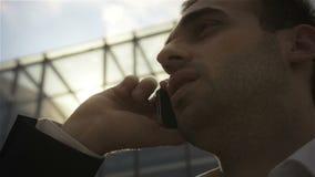 Close up do homem de negócios que está na frente da construção com telefone vídeos de arquivo