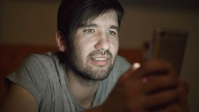 Close up do homem de sorriso novo que usa o smartphone para surfar os meios sociais que encontram-se na cama em casa na noite filme