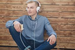 Close-up do homem escandinavo novo que guarda o telefone celular e a música de escuta com sorriso ao sentar-se no assoalho de mad fotos de stock
