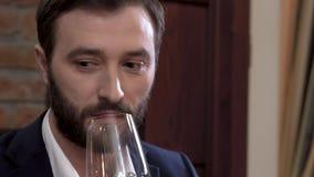 Close-up do homem farpado em um terno que prova um vidro do vinho branco filme