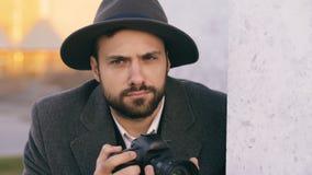 Close up do homem novo dos paparazzi no chapéu que fotografa celebridades na câmera quando espião atrás da parede imagens de stock