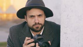Close up do homem novo dos paparazzi no chapéu que fotografa celebridades na câmera quando espião atrás da parede filme