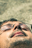 Close up do homem que dorme na praia Fotografia de Stock Royalty Free