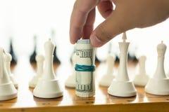 Close up do homem que faz o movimento no jogo de xadrez com cédulas torcidas Fotos de Stock Royalty Free