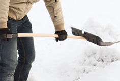 Close up do homem que trabalha com pá a neve da entrada de automóveis Imagem de Stock