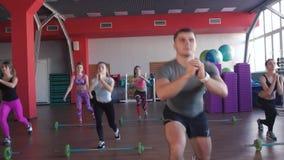 Close-up do instrutor masculino da aptidão Conduz uma lição da aptidão no gym aeróbio Todos executam ocupas video estoque