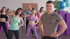 Close-up do instrutor masculino da aptidão Olha um grupo de meninas que treinam em um gym aeróbio filme