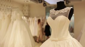 Close-up do manequim com vestido de casamento, assistente de loja que prepara vestidos de casamento para a venda em um boutique n video estoque
