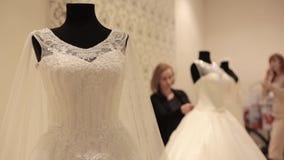Close-up do manequim com vestido de casamento, assistente de loja que prepara vestidos de casamento para a venda em um boutique n filme
